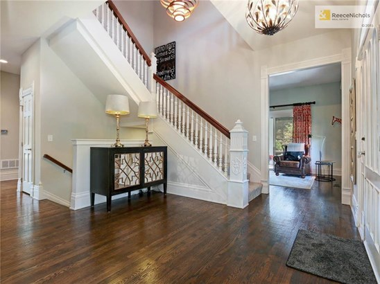 A dramatic two-story entry way with leaded glass doors and gleaming hardwoods speaks to the quality you will find throughout this unique home. (photo 2)