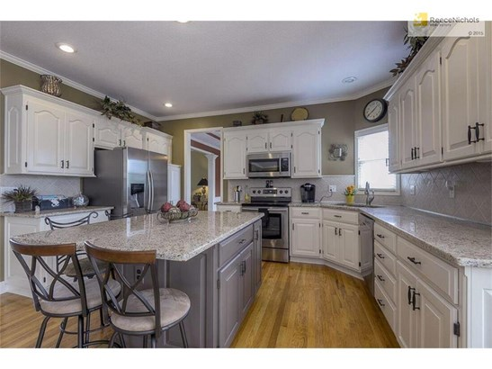 The stunning Kitchen boasts beautiful granite counters, tile backsplash, hardwood floors, and stainless steel appliances. (photo 4)