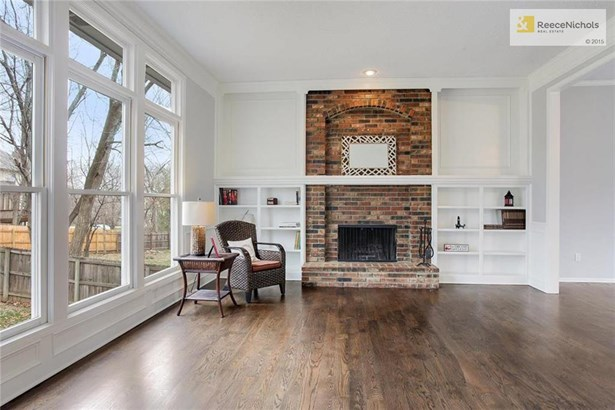 At the back of the home is the large open-concept family room, dining, and kitchen space. This space is open to the front living area, has a wonderful brick fireplace flanked with shelving, and a wall of large windows offering views into the backyard. (photo 5)