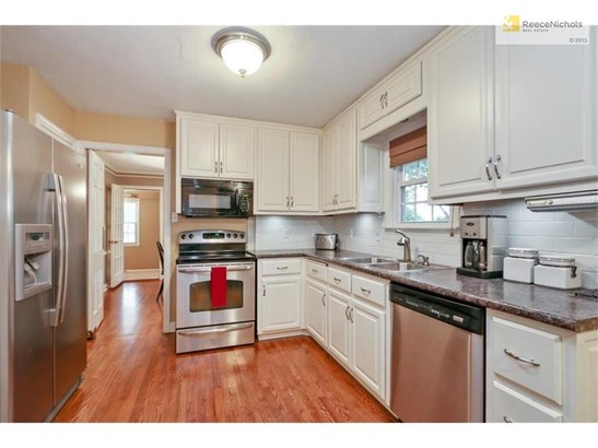The kitchen boasts white cabinets, pantry and stainless steel appliances (photo 5)