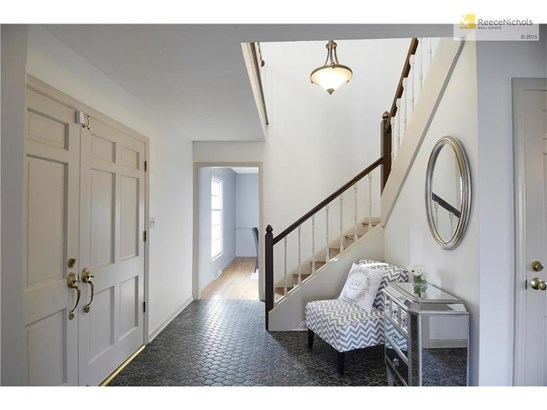 As soon as you enter the home you will find elegance and charm in the foyer which features stylish Quatrefoil tile and a grand L-shaped wood stair case. (photo 4)