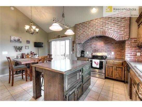 Tile flooring, custom brick vent hood, vaulted ceiling and an abundance of cabinets... (photo 3)