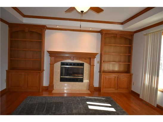 Fireplace flanked by built in book shelves (photo 3)
