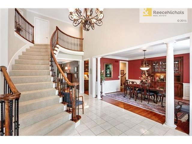 The large entry is enhanced by the curved staircase and wrought iron chandelier. (photo 2)