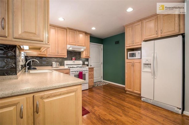 Remodeled kitchen with newer cabinets, appliances and solid surface counters. (photo 4)