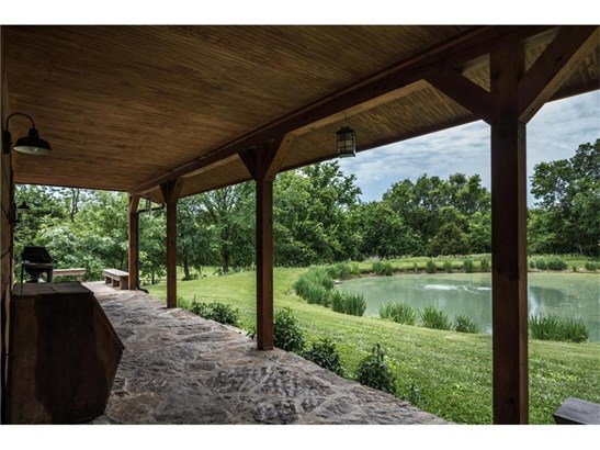 Real flagstone covers the floor of this wrap around porch.  Wood ceiling adds to the drama.  How many arrowheads can you find imbedded in this porch floor?   Fishing anyone?   Beautiful iris surround the pond. (photo 2)