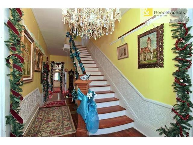 Original Lincrusta Walton wainscoting. Full plank stairs are solid and boast a beautiful custom rail. Entry features one of many dramatic chandeliers in the house. (photo 5)