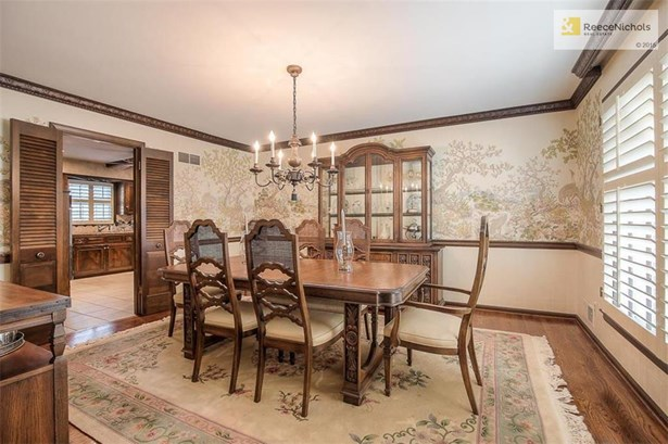 Formal dining room with intricately carved upper wood molding and mural wallpaper. (photo 3)
