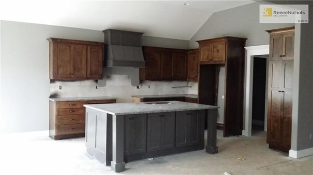 Fantastic kitchen with huge island (cabinets on both sides).  Doorway leads to laundry room, mud room, and three car garage. (photo 5)