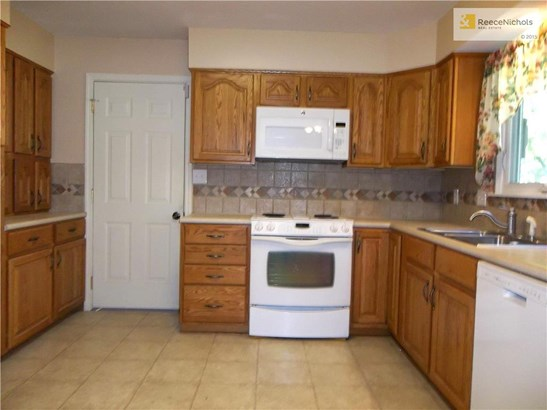 Kitchen with newer Back Splash, Electric Range, Micro-Wave, and Dishwasher. Door to Garage and Washer/Dryer. (photo 4)