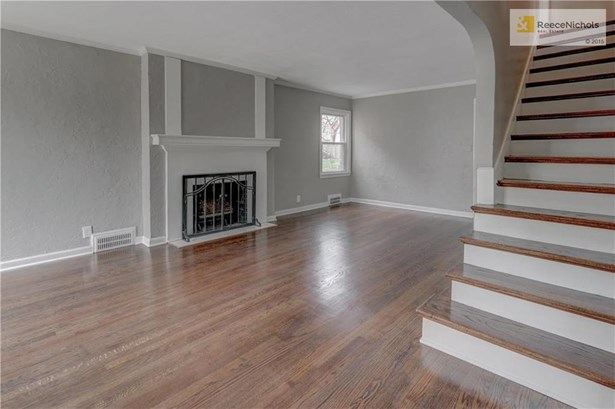 Large living room with cozy fireplace and beautiful refinished hardwood floors and new windows. (photo 4)