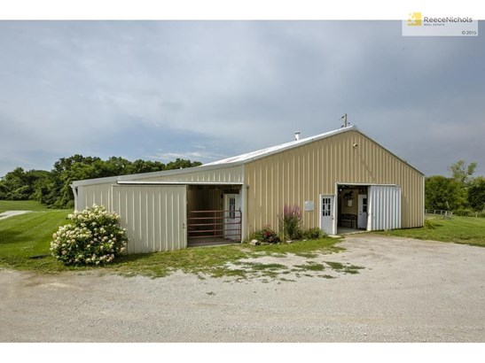 The arena barn is 115' x 65' and has nine 12' x 12' matted stalls, wash rack, tack room, laundry room, two grooming stalls, two frost-free hydrants, bath room with utility sink, 30 & 50 amp hook ups, 220 service, and shavings bin. (photo 4)