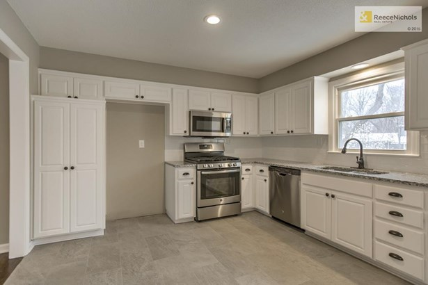 Kitchen with new cabinets, hardware, faucet, stainless steel appliances including a gas stove, tile flooring, backsplash and granite countertops. (photo 3)