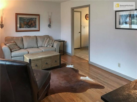 living room with hardwood floors and leads into the kitchen. (photo 3)