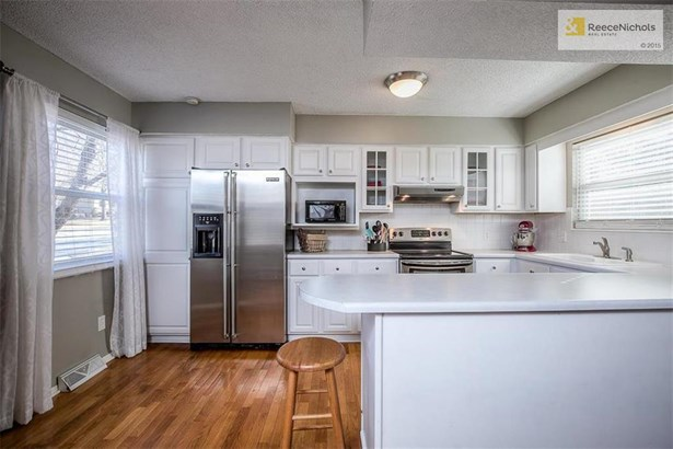 Light and bright kitchen with an abundance of countertop and cabinet space.  All the stainless steel appliances remain with the property. (photo 3)