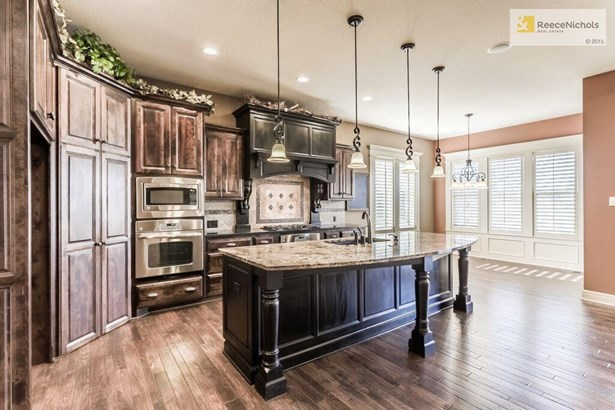 This kitchen has it all! Massive Island, Double Ovens, Gas Range, Soft Close Drawers and Cabinets, AND a walk in pantry that also has a work area/desk. (photo 5)