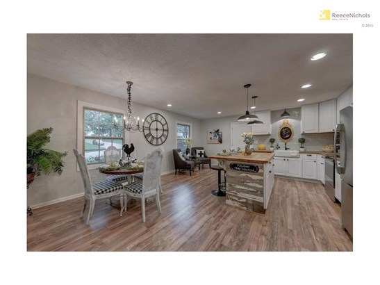 Hang out while the Chef whips up a gourmet meal!  Completely remodeled with white cabinets, butcher block counters, farm sink, tile back splash, stunning light fixtures, stainless appliances and large island. (photo 5)