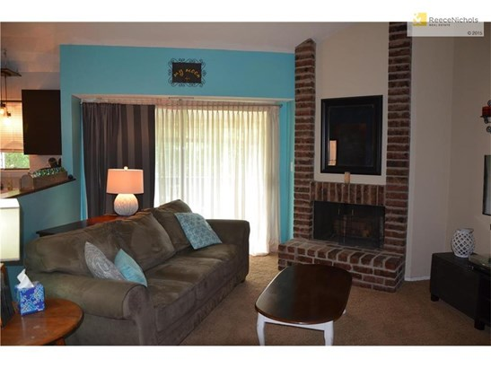 Great Room with corner fireplace and double sliders to covered balcony (photo 4)