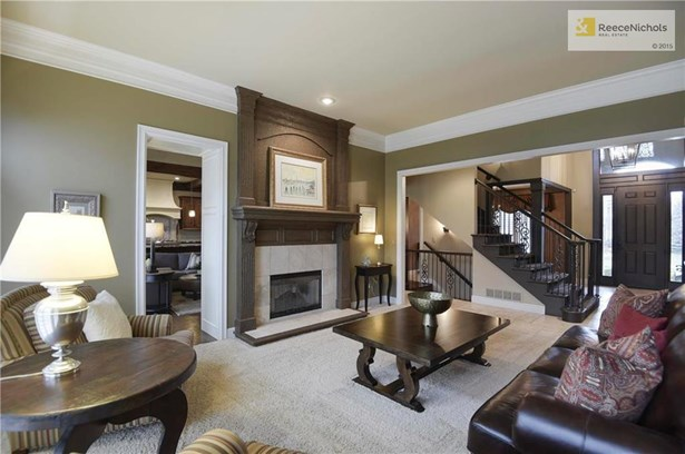 Spacious Living Room includes neutral carpet and see-through fireplace. (photo 5)