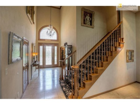 Two story travertine entry and open staircase to second level. (photo 5)