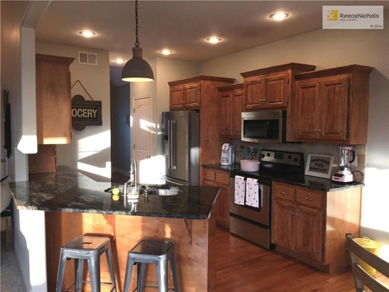 Granite counters, custom cabinets, stainless steel appliances, under-mount sink, tiled back splash, hardwood floors, two closet pantries. (photo 3)