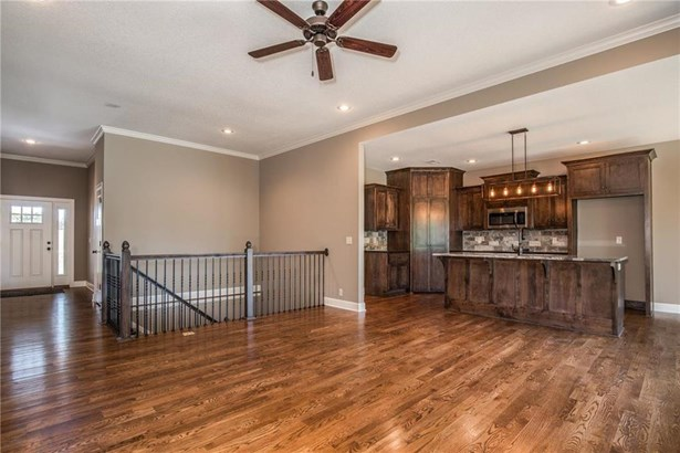 Gorgeous hardwood floors, stone fireplace with large mantel and ship lap wood trim above the mantle.  TV access above the mantle.  Switchback open staircase to the lower level.  10' ceilings in large entry and family room. (photo 5)