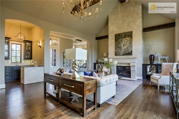 This house is perfect for entertaining. Your guests will love the stunning floor to ceiling fireplace accented by beams and the wet bar features a wine fridge, a sink, and beautiful cabinets - great for serving your guests! (photo 4)