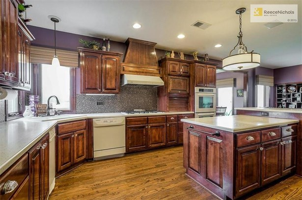 Hardwoods, custom cabinetry, flat surface counters, ceramic tile backsplash, subzero built-in refrigerator,  double ovens, and walk in pantry makes this a dream kitchen for any cook! Check out the updated hardware! (photo 4)