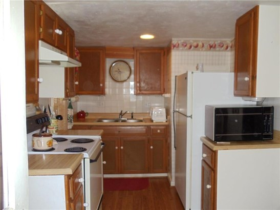 Kitchen with stove, refrigerator, microwave and toaster oven. Hot water heater closet left side of fridge (photo 3)