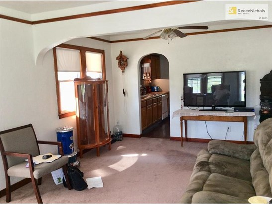 Living room has arched door into kitchen. (photo 2)