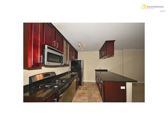 Tiled kitchen, stainless appliances including a gas stove (photo 1)
