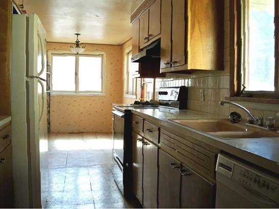 Galley kitchen with refrigerator, electric cook top range, dishwasher, garbage disposal, desk area, and utility closet. (photo 3)
