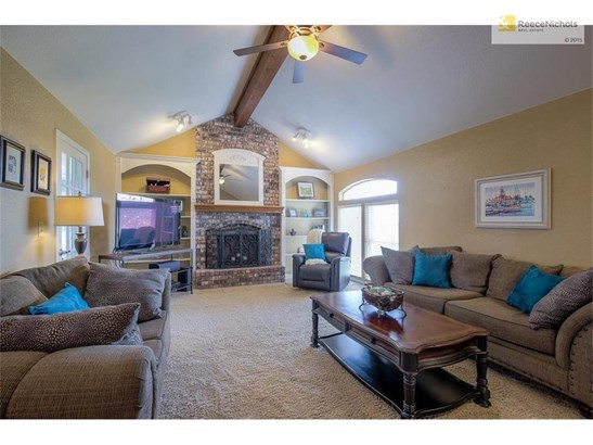 Great room with vaulted ceiling and fireplace.  Window looks out to landscaped backyard. (photo 4)