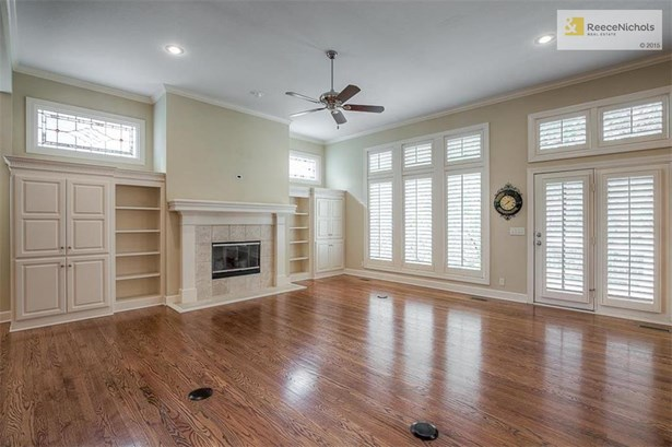 Great room with custom built-ins, fireplace and two floor outlets with floor to ceiling windows with plantation shutters and two stain glass windows plus doors to the outside deck & views of the heavily treed yard. (photo 5)