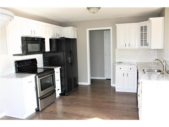 Kitchen with new flooring, new granite counter tops, and freshly painted cabinets (photo 5)