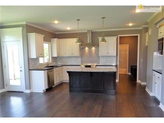Kitchen is complete with granite counter tops, center island, tiled back splash, smooth top slide in range with vented hood, snack bar with microwave & enameled cabinets. (photo 4)