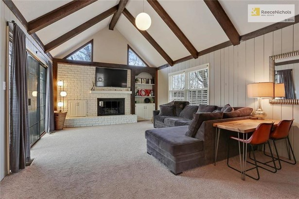 Charming family room is even better with its brick fireplace, built-ins, and exposed wood beams. (photo 5)