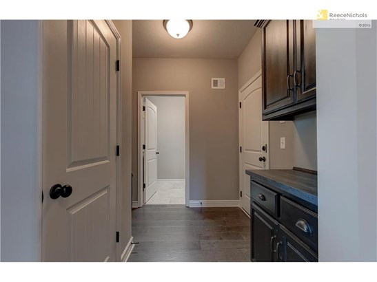 This Villa floor plan has such a convenient mud room. Adjacent to the front foyer as well as access to garage (door at right of photo). Counter space and cabinets to drop your mail and keys. Also, access to laundry room (top left of photo). (photo 5)