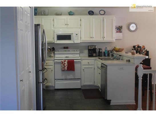 Kitchen with white cabinets, slate tile floor in kitchen and entry.  Laundry area behind double doors for convenience. (photo 3)