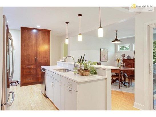 The kitchen is open to the dining and living areas, and has been updated with a center island, quartz counter tops, and a large built-in pantry. (photo 5)